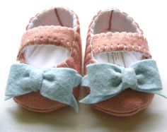 Coral Baby Shoes With Tiffany Blue Bows:  These gorgeous baby shoes, in a pale coral pink shade of wool felt for the body are accented with pretty Tiffany blue bows. The color combo is super sweet and unexpected. Each shoe is embellished with a hand crafted wool felt bow in the center. These shoes close using a hammered in CPSIA compliant snap for extra stay put goodness.