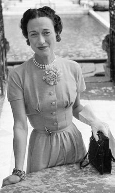 Black and White Photograph of Wallis Simpson sitting at a table with a handbag