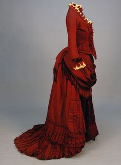 SILK and VELVET BUSTLE DRESS with FRINGE, c. 1880. Claret ottoman with self piping, lace and crenelated trim at neck, bib front and cuff, floral cut velvet bodice and skirt front panel, draped skirt trimmed in chenille fringe and pointed pleats, crocheted buttons, polished cotton lining. B-30, W-22, skirt front L-37, back L-52. (Faint underarm stains, two buttons need to be resewn, waistband replaced, train relined and altered to button on to skirt hem) very good