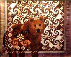 Janet Fogg -- Fabric featured: Multicolor -- Inspired by the book Undaunted Courage by Stephen Ambrose, this quilt features a life size grizzly bear stepping out of traditional Snails Trail and Rising Star Blocks. Machine pieced with some hand applique around the outer edge of the bear.
