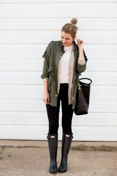 A green anorak jacket paired with a fuzzy cardigan, neutral top, leggings, and…