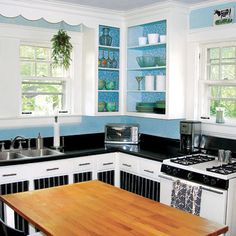 A coat of paint, new fabric panels and hardware, plus a butcher block island top refresh a bungalow cook space for less than $1,000. | Photo: Michelle Marburger | thisoldhouse.com