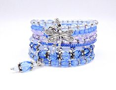 This beautiful blue wrap bracelet is made on 9 rows of silver memory wire and is filled with glass beads, crystals, glass Czech star beads, silver bead caps, 3 handmade crystal drops, and 2 silver dragonfly charms. ★ Return to my main shop page here for more inventory ★