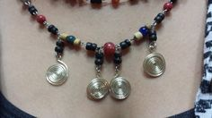 """Silver tone hammered, wire wrapped 1/2"""" hand worked swirls dangle from a  2mm-4mm multicolored (red, navy, beige, black) glass bead 22"""" necklace and 3"""" #coordinating earring... #trending #set #jewelry #vintage #statement #red #blue #tan #black"""