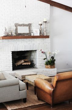 White painted brick fireplace - you still get the textured but it's toned down. Love the wood beam and all the neutral tones