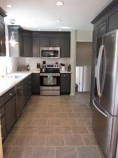 Painted charcoal grey kitchen cabinets, white countertops, and a white subway tile backsplash give this kitchen renovation updated style on a budget. Dark Grey Kitchen Cabinets, Gray And White Kitchen, Painting Kitchen Cabinets, White Cabinets, Stock Cabinets, Charcoal Kitchen, Neutral Kitchen, Kitchen Black, Kitchen Cupboards