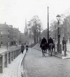Twee agenten te paard patrouilleren langs de Oostzeedijk in 1931. Links zie je de Sint-Lambertuskerk. Dit deel van Schielands Hoge Zeedijk ligt ten oosten van de oude stad. Het gedeelte van de dijk, dat als Hoogstraat, Schiedamsedijk en Vasteland bekend is, verbindt de Oostzeedijk met de Westzeedijk, die ten westen van de oude stad ligt. De dijk is rond het midden van de 13de eeuw aangelegd