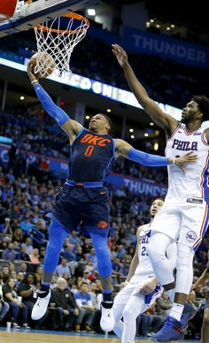 Oklahoma City's Russell Westbrook (0) goes up for a lay up as Philadelphia's Joel Embiid (21) defends during the NBA basketball game between the Philadelphia 76ers and Oklahoma City Thunder at Chesapeake Energy Arena, Sunday, Jan. 28, 2018. Photo by Sarah Phipps, The Oklahoman