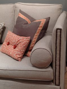 A beautiful sofa, with nail head detailing on the arms, is accessorized with Ryan Studio pillows.