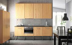 Eine moderne Küche mit HYTTAN Fronten in Eichenfurnier, ORRNÄS Griffen in Edelstahl und HÄLLESTAD Arbeitsplatten in Schwarz mit Metalleffektkante