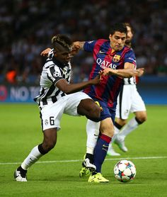 Luis Suarez of Barcelona is tackled by Paul Pogba of Juventus during the UEFA Champions League Final between Juventus and FC Barcelona at Olympiastadion on June 6, 2015 in Berlin, Germany.