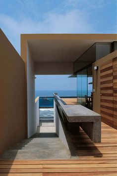 wood and concrete residence w/ glass pool overlooking ocean