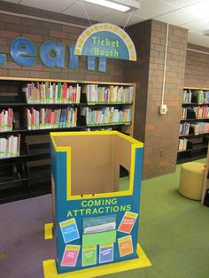 Play and Learn at the library; Arts theme - Ticket Booth for dramatic play. Kids crawl in and sell tickets for performances held on the stage. The box on front holds Cards that can be swapped to say one of six types of performance such as dance recital, comedy show, music concert, etc.