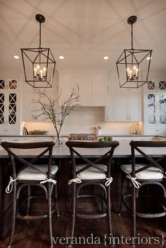 Love the pendant lighting.... White shaker style kitchen, with cross mullions on glass doors, dark floors and pendant lighting