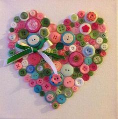 Los corazones son corrientes en button art o técnica de realizar cuadros con botones pegados o cosidos a un lienzo. Bonita combinación de colores terminada con un lazo decorativo.