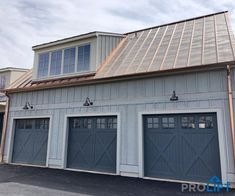 These farmhouse, barn-inspired, wooden garage doors by Artisan are beautifully crafted with Red Grandis and custom painted to complement the new home construction. Notice the farmhouse style lights above each door to polish off the look.  | Pro-Lift Garage Doors of St. Louis on Houzz | Photo Credits:  Pro-Lift Garage Doors Va #garagedoors