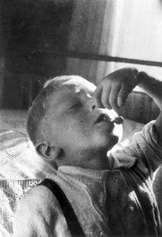 Lodz, Poland, A child eating cherries in the ghetto. Mendel Grosman