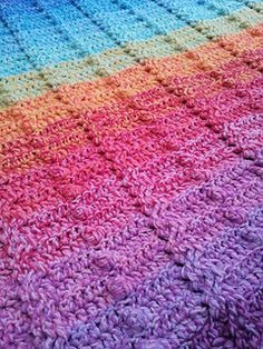 Cable and bobble stitch blanket in gradient rainbow colors using 3 strands held together by Dedri Uys