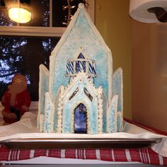 Disney Frozen gingerbread house castle. Gingerbread was frosted with icing and then sprinkled with white and blue sugar. The upstairs balcony is made with melted blue Jolly Ranchers. Elsa, Anna & Olaf can be seen through the upstairs window. Sven and Kristoff are seen through the lower door. Xmas 2014 for Leah & Allie