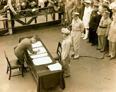 Japanese representatives of Emperor Hirohito sign the final surrender documents ending World War II, aboard the battleship Missouri in Tokyo Bay, with General MacArthur and other Allied leaders looking on.
