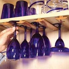 DIY Kitchen Storage Solutions: Use T-molding to hold stemware – T-molding designed for wood floor transitions makes a perfect rack for stemware. Just cut it to length, pre-drill screw holes and screw it to the underside of a shelf. For a neater look, use brass screws and finish washers. Pre-finished T-molding is available wherever wood flooring is sold. A 4-ft. section costs about $25