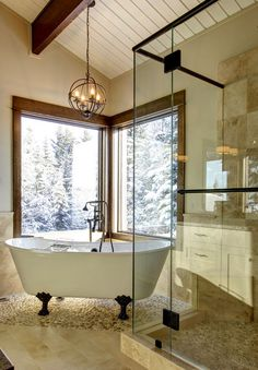 frameless shower and vaulted/exposed beam ceiling for a feel of spaciousness and stand alone tub on pebble floor.
