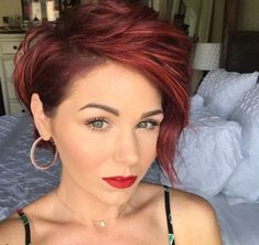 close up shot of woman with a tousled short red cherry pixie cut, wearing hoop earring and posing in a bedroom
