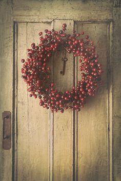 Berry wreath hanging on old wood door by Sandra Cunningham. I'm loving this for my Christmas décor, its very old New England preppy elite. Less is more!