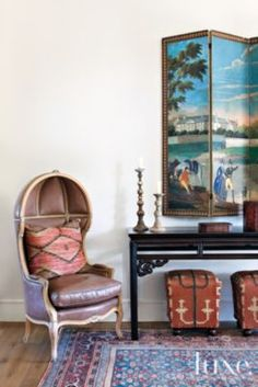 An 18th-century French painted screen hangs above an exotic Indonesian console in this vignette of the formal living room.