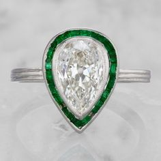 This vintage diamond engagement ring with emerald halo features an incredible 1.57 ct antique pear cut diamond surrounded by a halo of calibre cut emeralds!