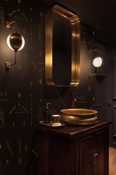 dark wood cabinet, black patterned walls and brass decorations