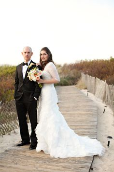 The couple poses in the sand of this classic Cape Cod wedding.