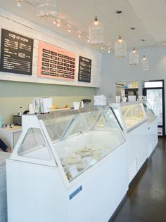 this is an ice cream store, but I love the decor--mint green penny tile, pop of coral, milk bottle lights, dark floor via yhl