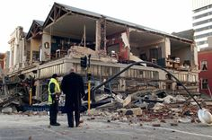 """""""People stand outside a building damaged by a 7.4-magnitude earthquake in central Christchurch, New Zealand, early Saturday"""". [The Christchurch Star, Sept. 4, 2010]"""