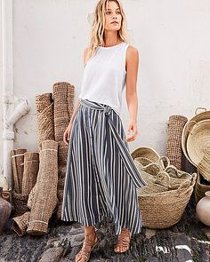Vertical stripes accentuate the figure with the allure of a high-rise waist and midi length. To change things up, cinch the waist tie — and undo a few buttons up the hem.
