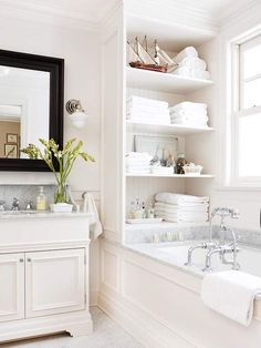 a wonderful use of built in storage above a bathtub!