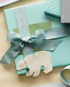 This felt animal makes a fanciful gift topper. Choose from a polar bear, cat, seal, wolf, mouse, fish, or bear. Get the templates for them. Silk Moire ribbon (#20001), Color #23, Width #25; mokubany.com. Aqua Matelasse Wrap, bellocchio.com.