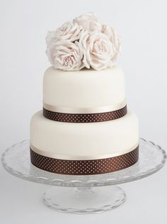 Wedding cake. Simple smaller bouquet on top and  band on color of maid of honor dress