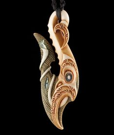 "Medium: bone, pāua (New Zealand abalone). Size: 3.5 x 1.25 inches. Tangaroa Kaiwhangai Nui (Tangaroa Great Provider): ""In this piece, I pay homage to the great oceans of the world, the realm of Tangaroa, in this instance personified by the presence of the Marakihau (sea monster) and the great whirlpool, Korokoro o te Parata, from whence, it is told the massive ocean swells originate. "" David Taylor."