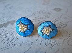 青い花のピアスです。左右で少し違う色で刺繍しました。真ん中は白と黄色のシードビーズです。ウラの金具に被せた合皮を縫う糸の色合いにもこだわっています。このシリー...|ハンドメイド、手作り、手仕事品の通販・販売・購入ならCreema。