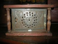 A wonderful red painted footwarmer with a heart motif on its tin panels and its little coal pan inside.