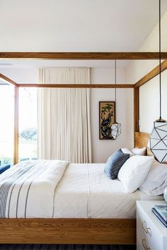 Bedroom with a birch canopy bed and low-hanging pendant lights