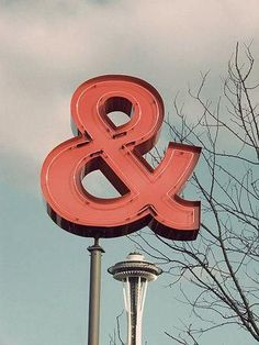 red florescent & and ampersand not fluorescing  against a clouded blue sky with the space needle & some barren trees Seattle Pacific Northwest
