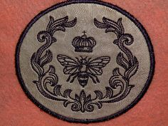 A royal patch, Queen Bee with Parisian Laurel is stitched on silver leather with royal purple threads. This patch measures 4.25 wide by 3.9 high.
