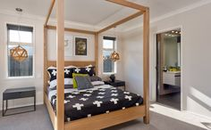 A modern four poster uses this master bedrooms space well and looks good.