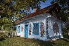 The secluded village of Zalipie in southeastern Poland is home to a charming tradition. Over a century ago the women of the village began to paint their houses. Every house is painted with flowers. Wooden Cottage, Painted Cottage, Painted Houses, White Cottage, Casa Pop, Most Beautiful, Beautiful Places, Glass Building, House Painting