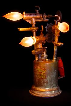 """Pop's Torch""    Hand crafted from brass kerosene torches, a dimmer has been retrofitted into the original air pump and electricity is controlled by rotating the pump handle clockwise. (w:9"" h:16"" d:11"")    $575.00"