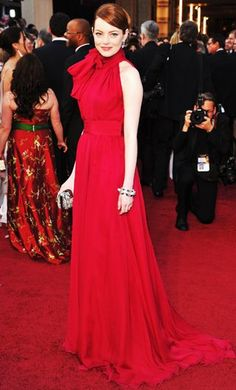 Emma Stone presented at the 2012 Academy Awards in a lovely Giambattista Valli gown with a dramatic oversized neck tie. We love that color on the redhead. Louis Vuitton jewels and minaudiere were dazzling complements.