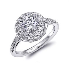 Elegant and romantic, this engagement ring highlights a floral inspired halo framed with milgrain edging. Diamonds adorn the shank adding more sparkle to this captivating piece. Shown with a 1 CT center stone.