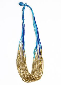 Dress it up or go casual, this rainfall of golden beads flows along azure and cobalt threads to stylishly grace the neck. Handmade by a fair trade artisan group in India that creates avenues of employment for the economically disadvantaged. #noondaystyle
